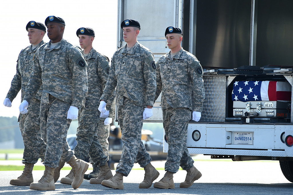. U.S. Army soldiers walk away from the transfer vehicle after carrying the flag-draped transfer case containing the remains of U.S. Army Maj. Gen. Harold J. Greene during a dignified transfer at Dover Air Force Base on August 7, 2014 in Dover, Delaware.  (Photo by Patrick Smith/Getty Images)