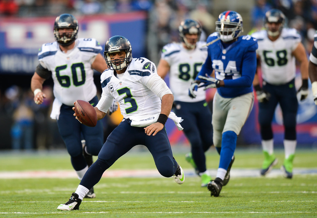 . Quarterback Russell Wilson #3 of the Seattle Seahawks runs with the ball in the 1st half against the New York Giants at MetLife Stadium on December 15, 2013 in East Rutherford, New Jersey. (Photo by Ron Antonelli/Getty Images)