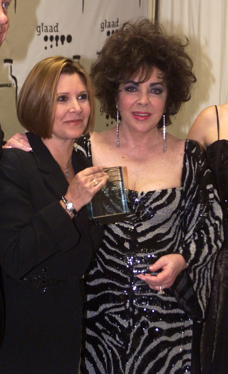 . Carrie Fisher, left, holds the Vanguard Award she presented to Elizabeth Taylor backstage at the 11th Annual GLADD (Gay and Lesbian Alliance Against Defamation) Media Awards held in the Century City section of Los Angeles, Saturday, April 15, 2000. AP Photo/Jill Connelly)