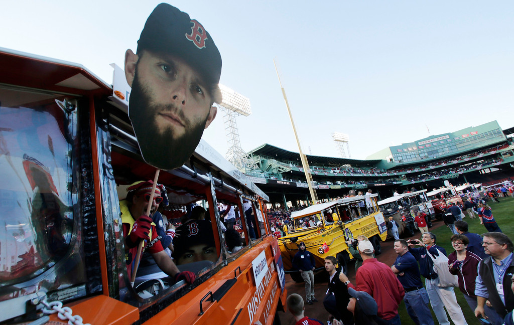 . A giant head photograph of Boston Red Sox\'s Dustin Pedroia is held out of a duck boat at Fenway Park as they prepare to leave for a parade in celebration of the baseball team\'s World Series win, Saturday, Nov. 2, 2013, in Boston. (AP Photo/Charles Krupa)