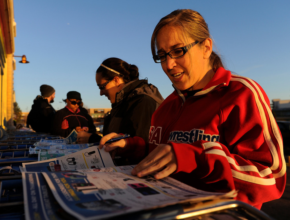 . Anne Whipple, right, and her sister Mary DeLisa, center, went through advertising flyers as they planned out a night of shopping while waiting in line outside the Toys R Us store on County Line Road in Arapahoe County Thursday night, November 28, 2013. Photo By Karl Gehring/The Denver Post