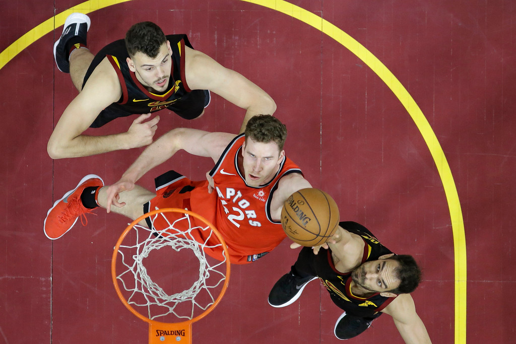 . Toronto Raptors\' Jakob Poeltl, center, from Austria, drives to the basket against Cleveland Cavaliers\' Ante Zizic, left, from Croatia, and Cleveland Cavaliers\' Jose Calderon, from Spain, in the second half of Game 4 of an NBA basketball second-round playoff series, Monday, May 7, 2018, in Cleveland. The Cavaliers won 128-93. (AP Photo/Tony Dejak)
