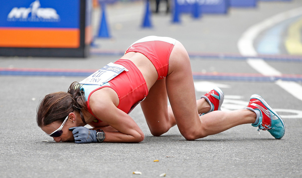 . Sabrina Mockenhaupt of Germany kisses the ground after finishing seventh in the women\'s division of the New York City marathon, Sunday, Nov. 3, 2013, in New York. (AP Photo/Kathy Willens)