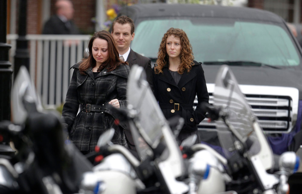 Description of . Mourners walk past police motorcycles as they depart St. Patrick's Church in Stoneham, Mass., following a funeral Mass for Massachusetts Institute of Technology police officer Sean Collier, Tuesday, April 23, 2013. Collier was fatally shot on the MIT campus Thursday, April 18, 2013. Authorities allege that the Boston Marathon bombing suspects were responsible. A truck that belonged to Collier sits behind. (AP Photo/Steven Senne)