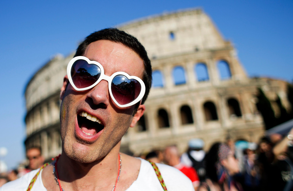 . A man poses in front of the Colosseum during the annual gay pride parade in downtown Rome June 15, 2013. REUTERS/Max Rossi