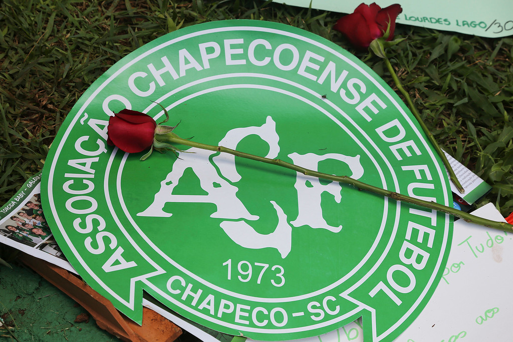 . A red rose sits on top of the Chapecoense soccer team logo outside the Arena Conda stadium, where team fans are gathering in Chapeco, Brazil, Tuesday, Nov. 29, 2016. A chartered plane that was carrying the Brazilian soccer team Chapecoense to the biggest match of its history crashed into a Colombian hillside and broke into pieces, Colombian officials said Tuesday. (AP Photo/Andre Penner)