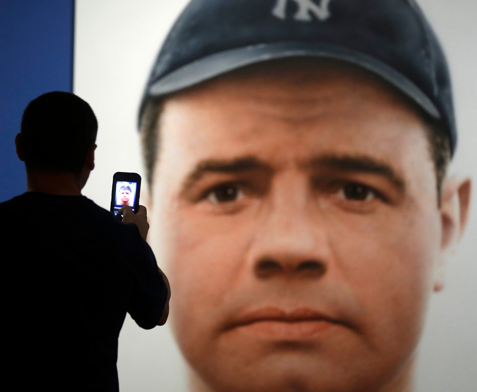 . A man photographs a portrait of Babe Ruth at the Baseball Hall of Fame on Saturday, July 27, 2013, in Cooperstown, N.Y. Jacob Ruppert, Hank O�Day and Deacon White will be inducted posthumously to the hall on Sunday. The three men represent the Class of 2013 and they\'ve all been dead for more than 70 years, making Sunday\'s festivities something out of the ordinary. (AP Photo/Mike Groll)