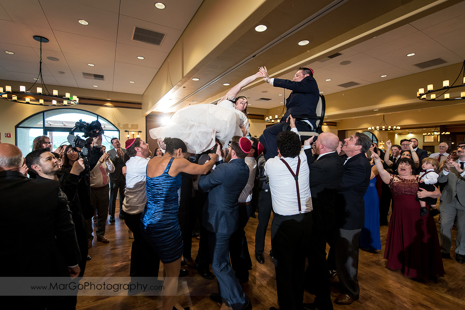 jewish bride and groom lifted on the chairs during horah dance at Livermore Garre Vineyard and Winery