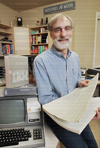Tim Paterson, the original author of disk operating system (DOS), is pictured holding a era-printout of DOS code he authored, as seen in his home office in Issaquah, Washington