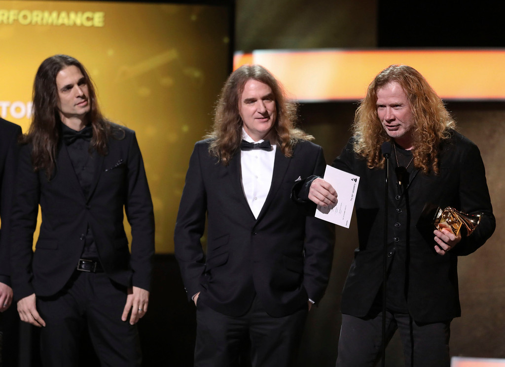 ". Kiko Loureiro, from left, David Ellefson, and Dave Mustaine of ""Megadeth\"" accept the award for best metal performance for \""Dystopia\"" at the 59th annual Grammy Awards on Sunday, Feb. 12, 2017, in Los Angeles. (Photo by Matt Sayles/Invision/AP)"