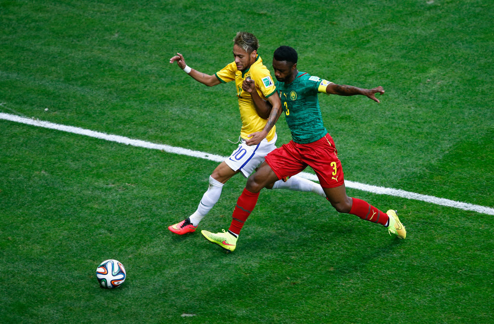 . Neymar of Brazil competes for the ball with Nicolas N\'Koulou of Cameroon during the 2014 FIFA World Cup Brazil Group A match between Cameroon and Brazil at Estadio Nacional on June 23, 2014 in Brasilia, Brazil.  (Photo by Phil Walter/Getty Images)