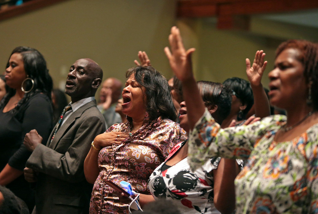 . People attending the funeral services for Michael Brown sing on Monday, Aug. 25, 2014, at Friendly Temple Missionary Baptist Church in St. Louis. Brown, who is black, was unarmed when he was shot in Ferguson, Mo., Aug. 9 by Officer Darren Wilson, who is white. Protesters took to the streets of  the St. Louis suburb night after night, calling for change and drawing national attention to issues surrounding race and policing. (AP Photo/St. Louis Post Dispatch, Robert Cohen, Pool)