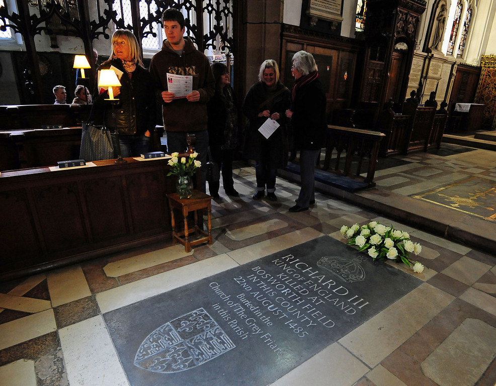 ". People stand near the memorial stone to King Richard III, inside Leicester Cathedral, England, Monday Feb. 4, 2013. Leicester University declared Monday that the remains  found underneath a car park last September at the Grey Friars excavation in Leicester, were ""beyond reasonable doubt\"" to be the long lost remains of England\'s King Richard III, missing for 500 years.  Richard was immortalized in a play by  Shakespeare as a hunchbacked usurper who left a trail of bodies including those of his two young nephews, murdered in the Tower of London on his way to the throne.(AP Photo/PA, Rui Vieira)"
