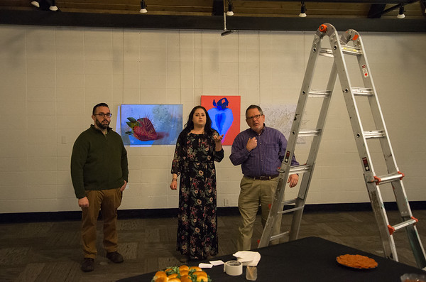 03/22/19 Wesley Bunnell | Staff A mixed media art exhibit kicked off on Friday night at Stockman Gallery by artist Megan Antosik Lavoie titled Food Circus which explores the artists food allergies and relationship with food. The artist, center, stands with her husband Bob, L, and Stockman Gallery Manager Stephen Hard as they make last minute changes to her exhibit.