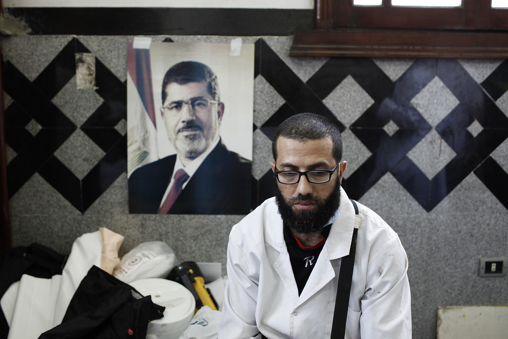 . CAIRO, EGYPT - JULY 27:  A member of the medical staff of a field hospital sits in front of a poster of deposed Egyptian President Mohammed Morsi after tending to the bodies of pro-Morsi supporters reportedly killed in fighting between pro-Morsi demonstrators and Egyptian security forces overnight, near the Rabaa al Adweya Mosque in the district of Nasr on July 27, 2013 in Cairo, Egypt.  Morsi supporters had gathered at a sit in protest in Nasr City on Friday to continue demonstrations against the overthrow of Morsi, Egypt\'s first democratically elected leader, on July 3 by the Egyptian Armed Forces. Muslim Brotherhood leaders had called for pro-Morsi protesters to return to the streets on Friday in response to a speech made Wednesday by the Chief of Egypt\'s Armed Forces, General Abdel Fattah al-Sissi, who called for mass pro-military protests across Egypt on Friday against \'violence and terrorism\' and in support of the military\'s overthrow of Morsi. (Photo by Ed Giles/Getty Images)
