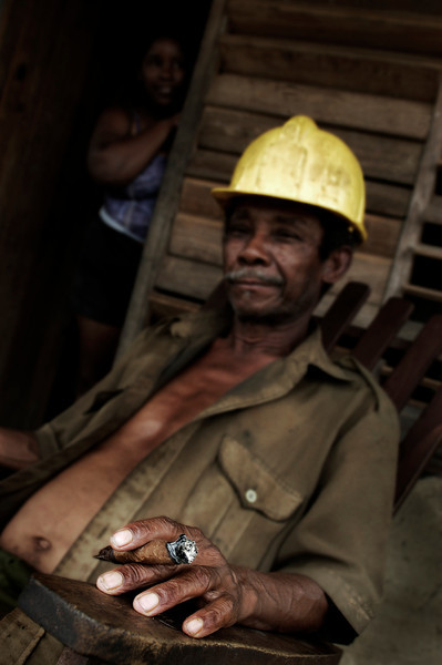 Worker relaxing with a cigar outside his home. Wife in the background, Vinales, 