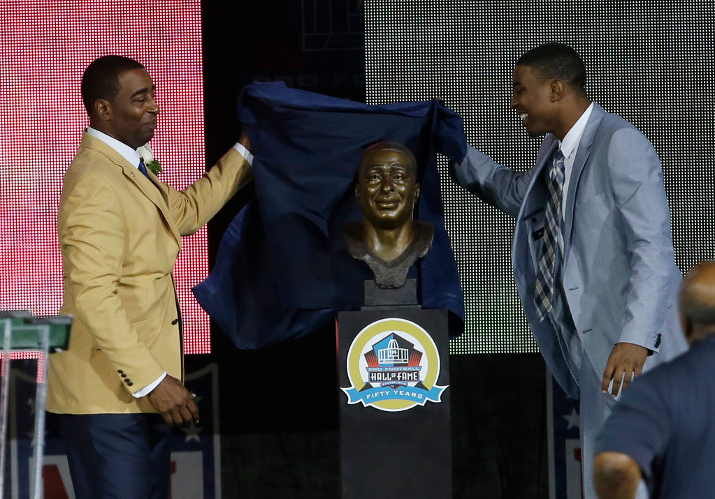 . Former NFL football player Chris Carter, left, and his son, Duron, unveil Carter\'s bust  during the induction ceremony at the Pro Football Hall of Fame Saturday, Aug. 3, 2013, in Canton, Ohio. (AP Photo/Tony Dejak)