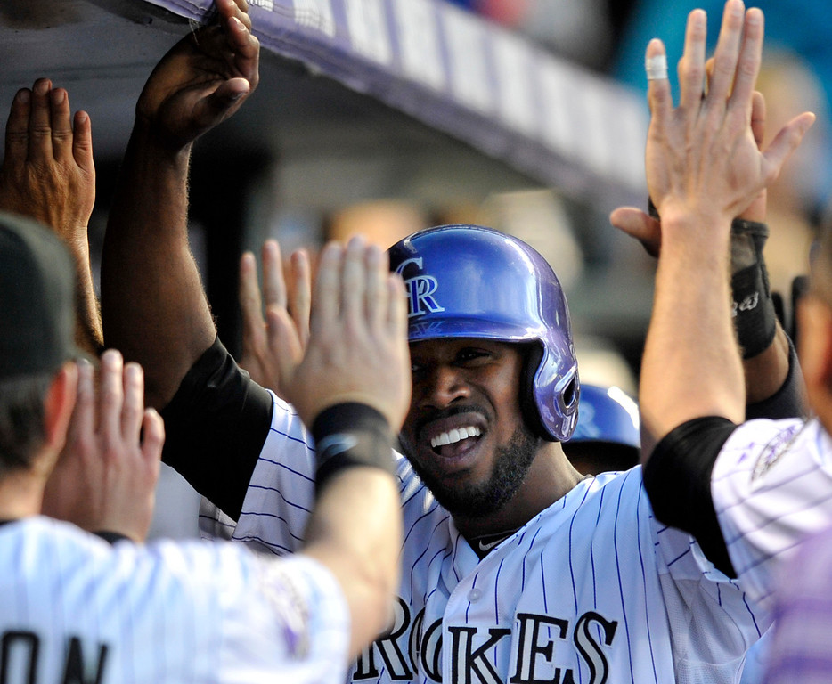 . Colorado Rockies\' Dexter Fowler, center, is congratulated by teammates after scoring on a Carlos Gonzales two run triple against the San Francisco Giants during the third inning of a baseball game on Friday, May 17, 2013, in Denver. (AP Photo/Jack Dempsey)