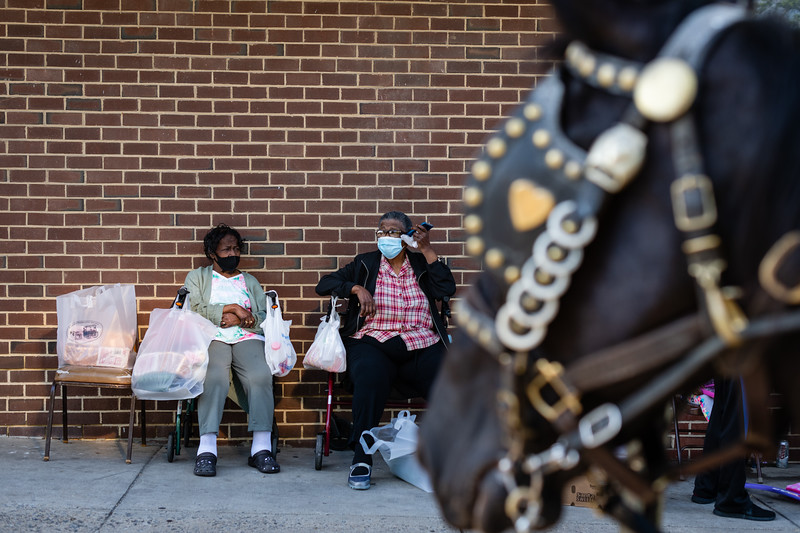 Residents at the Harvey Johnson Tower sit outside after getting groceries from the arabbers.