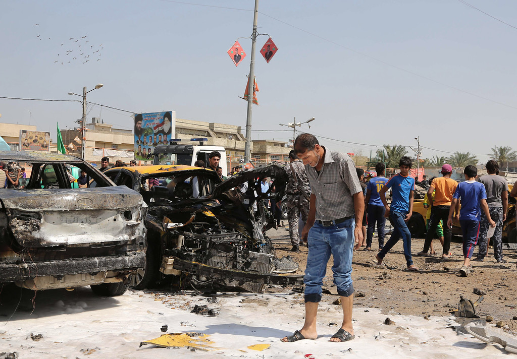 . Civilians inspect the site of a car bomb explosion in the Shiite stronghold of Sadr City, in Baghdad, Iraq, Tuesday, May 13, 2014.(AP Photo/Karim Kadim)
