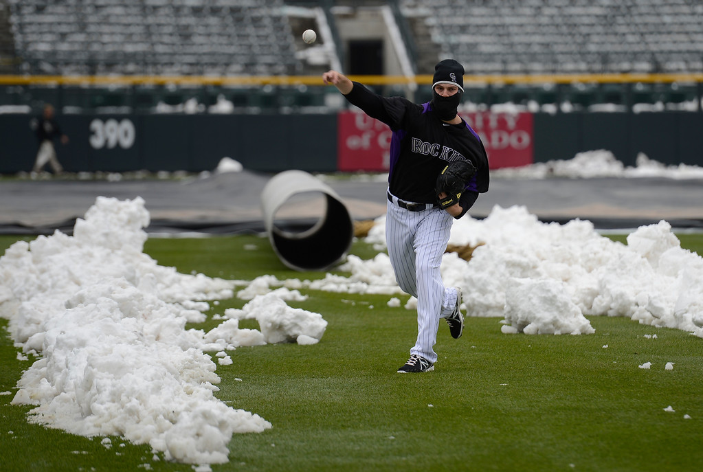 . Adam Ottaavino (0) of the Colorado Rockies  warms up with the pile of snow in right field as a backdrop. Rockies grounds crew and employees work to clear the field of snow to get the first game of a double header in against the  New York Mets April 16, 2013 at Coors Field. (Photo By John Leyba/The Denver Post)