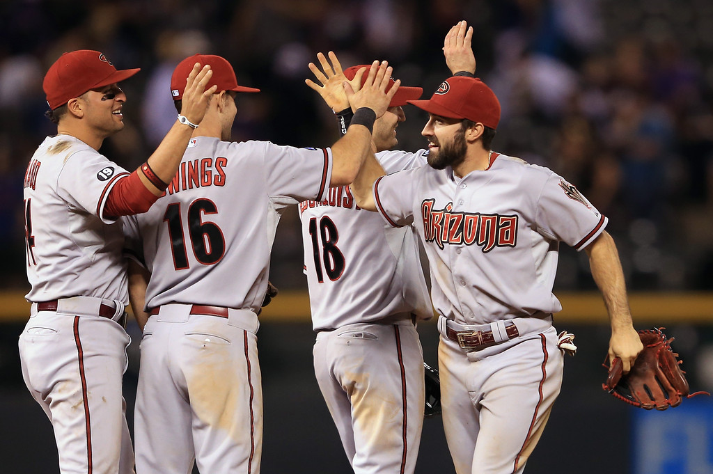 . DENVER, CO - SEPTEMBER 21:  (L-R) Martin Prado #14, Chris Owings #16, Willie Bloomquist #18 and Adam Eaton #6 of the Arizona Diamondbacks celebrate their 7-2 victory over the Colorado Rockies at Coors Field on September 21, 2013 in Denver, Colorado.  (Photo by Doug Pensinger/Getty Images)