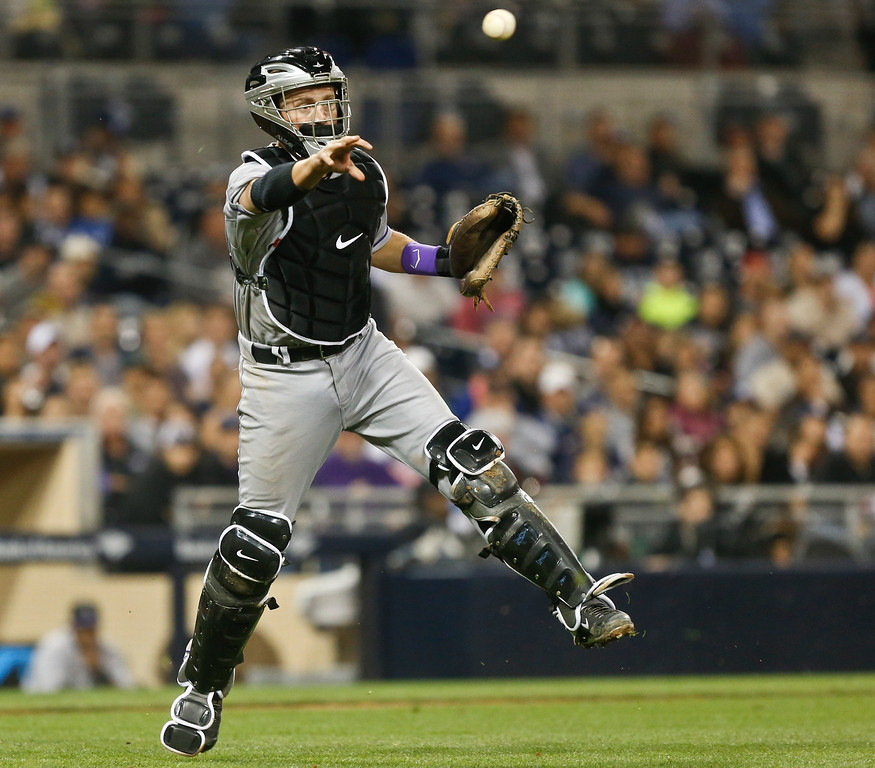 . Colorado Rockies pitching coach Jim Wright makes the throw to first to get San Diego Padres\' Andrew Cashner at first base in the fifth inning of a baseball game Wednesday, April 16, 2014, in San Diego.  Cashner\'s bunt moved a runner into scoring position who later scored.   (AP Photo/Lenny Ignelzi)