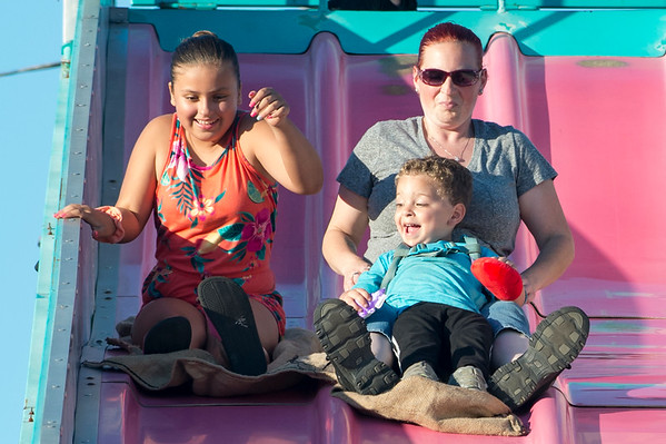 07/12/19 Wesley Bunnell | Staff Olivia Marquez, age 11, L goes down the Super Slide along with Angel Dickinson and son, MJ, age 3, at the Holy Cross Bazaar on Friday July 12, 2019.