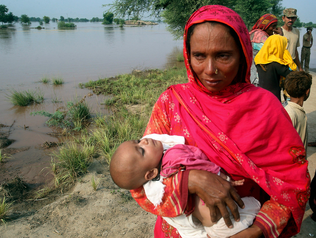 . A mother carrying a child cries while evacuating her home along the flooded Chenab River, in Jhang, Pakistan, Wednesday, Sept. 10, 2014. Thousands of people fled their homes in Pakistan on Wednesday as monsoon flooding that has already inundated the disputed Himalayan region of Kashmir coursed down onto the plains, causing the Chenab River to breach its banks.   (AP Photo/K.M. Chaudary)