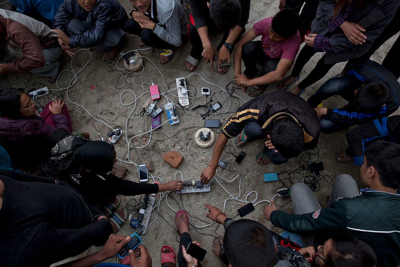 . Nepalese villagers charge their cell phones in an open area in Kathmandu, Nepal, Monday, April 27, 2015. Shelter, fuel, food, medicine, power, news, workers ó Nepal\'s earthquake-hit capital was short on everything Monday as its people searched for lost loved ones, sorted through rubble for their belongings and struggled to provide for their families\' needs. (AP Photo/Bernat Armangue)