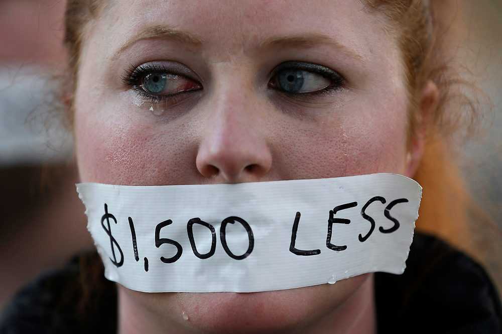 Description of . A silent protester cries while wearing a sticker over her mouth signifying the loss in wages from the right-to-work law in Lansing, Mich., on Wednesday, Dec. 12, 2012. Michigan became the 24th state with a right-to-work law after Gov. Rick Snyder signed the bill Tuesday. (AP Photo/Paul Sancya)