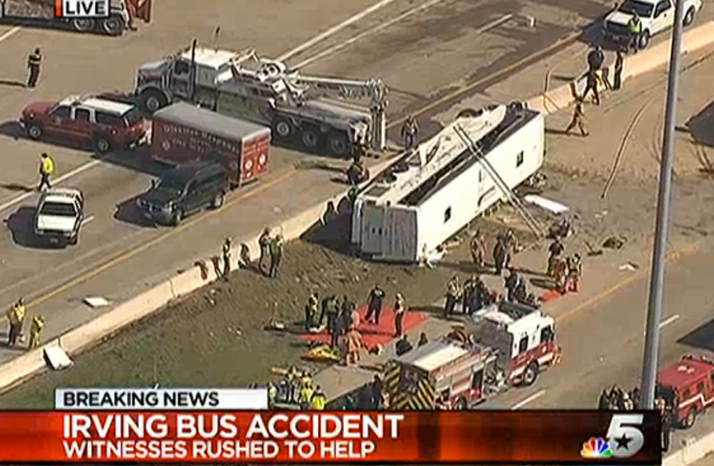 . This frame grab provided by KXAS-TV shows emergency personnel at the scene where a chartered bus overturned on a highway near Dallas-Fort Worth International Airport in Irving, Texas.  Authorities say at least six people are hospitalized.  (AP Photo/Courtesy KXAS-TV)