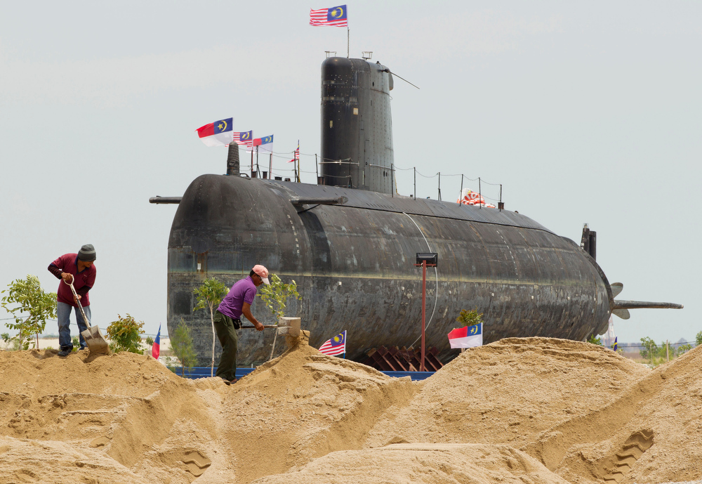 . Workers at construction site shovel sand with the decommissioned Agosta 70 class submarine, the SMD Ouessant, sitting behind in Melaka, Malaysia, Wednesday, March 7, 2012. Built in 1979, the French made submarine was the Royal Malaysian Navy training submarine and will now be a feature at Melaka\'s Submarine Museum. (AP Photo/Mark Baker)