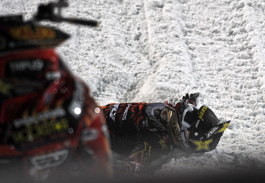 . In this photo taken Jan. 24, 2013, Caleb Moore lies in the snow after he crashed during the snowmobile freestyle event at the Winter X Games in Aspen, Colo. (AP Photo/The Colorado Springs Gazette, Christian Murdock) MAGS OUT