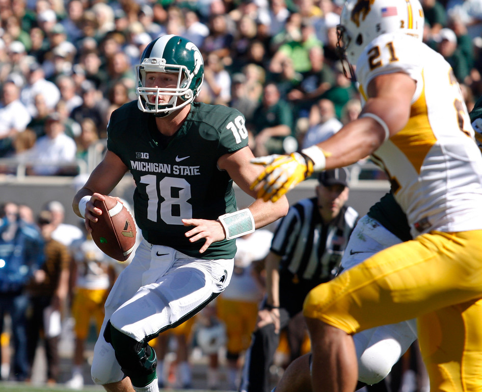 . Michigan State quarterback Connor Cook (18) scrambles for a touchdown on a keeper against Wyoming\'s Mark Nzeocha during the first quarter of an NCAA college football game, Saturday, Sept. 27, 2014, in East Lansing, Mich. Michigan State won 56-14. (AP Photo/Al Goldis)