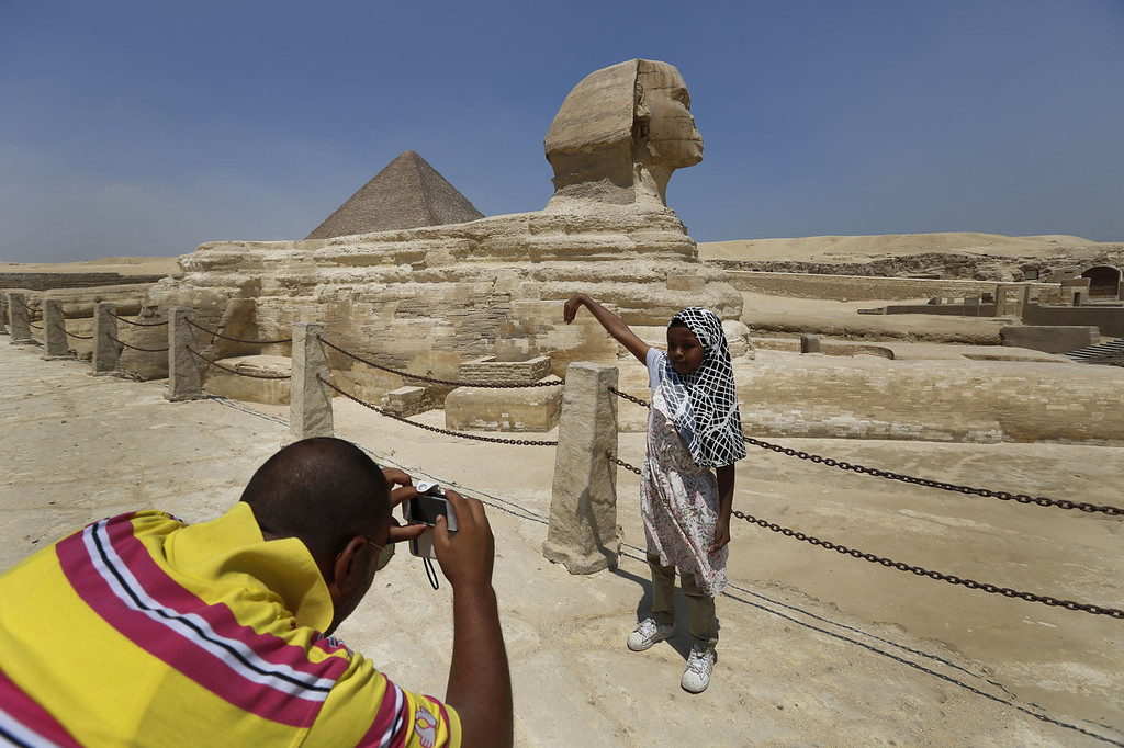 . A tourist poses for a photograph in front of the Great Sphinx, at the the historical site of the Giza Pyramids, background, near Cairo, Egypt, Tuesday, Aug. 27, 2013. The chairman of the Egyptian Airports Co. says some flights are arriving nearly empty to Egypt and that passenger traffic in the past week has fallen by half. Due to the country\'s violent turmoil, some flights that can carry more than 100 passengers from Europe arrive with just nine and return full from beach resorts. (AP Photo/Lefteris Pitarakis)