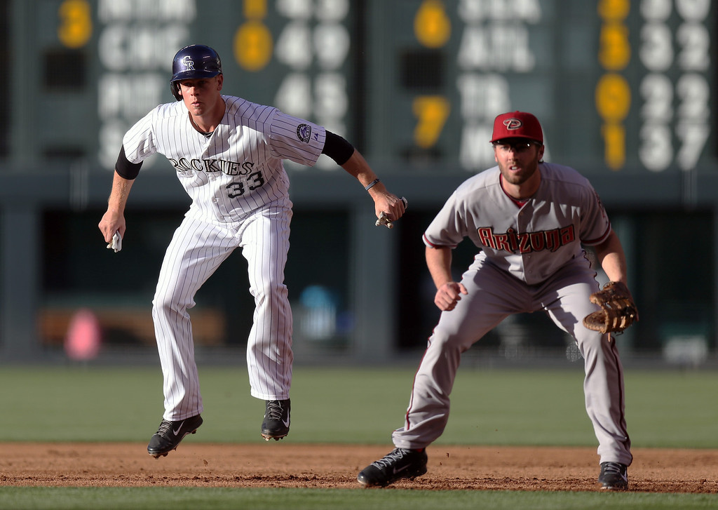 . Colorado Rockies base runner Justin Morneau, left, jumps in the air as he takes a lead off first base as Arizona Diamondbacks first baseman Nick Evans covers in the first inning of a baseball game in Denver on Tuesday, June 3, 2014. (AP Photo/David Zalubowski)