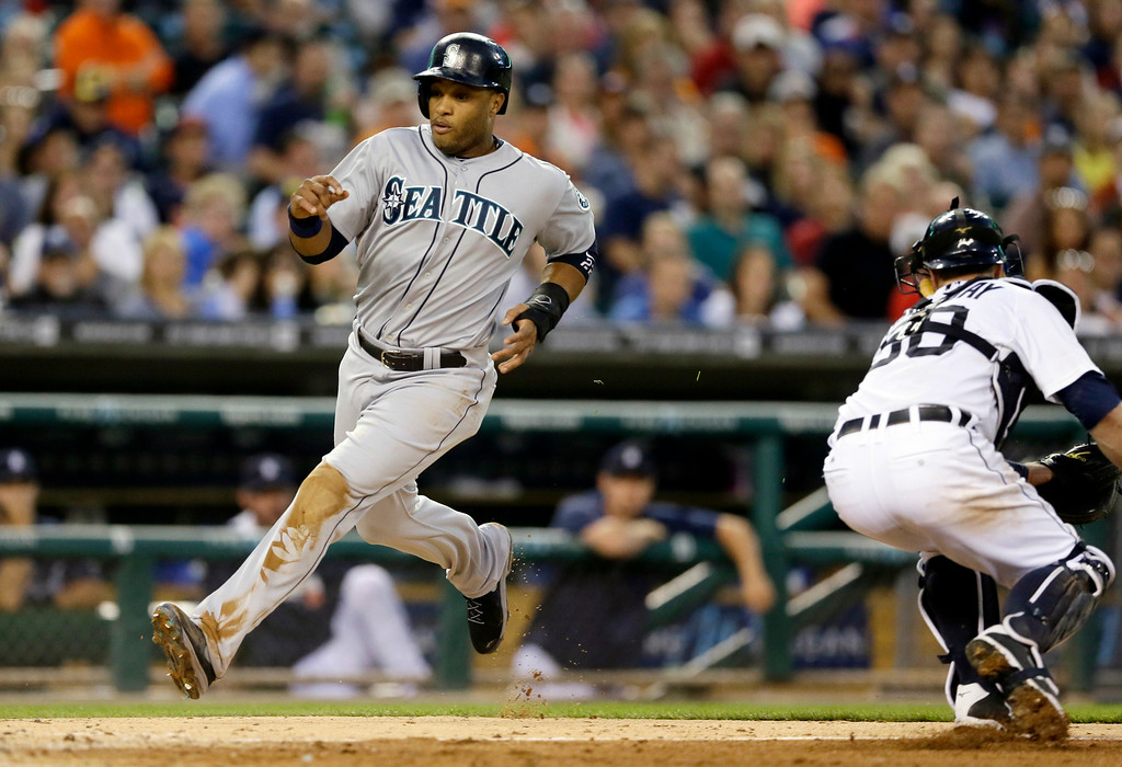 . Seattle Mariners\' Robinson Cano safely avoids the tag of Detroit Tigers catcher Bryan Holaday, right, and scores during the fifth inning of a baseball game, Friday, Aug. 15, 2014 in Detroit. (AP Photo/Carlos Osorio)
