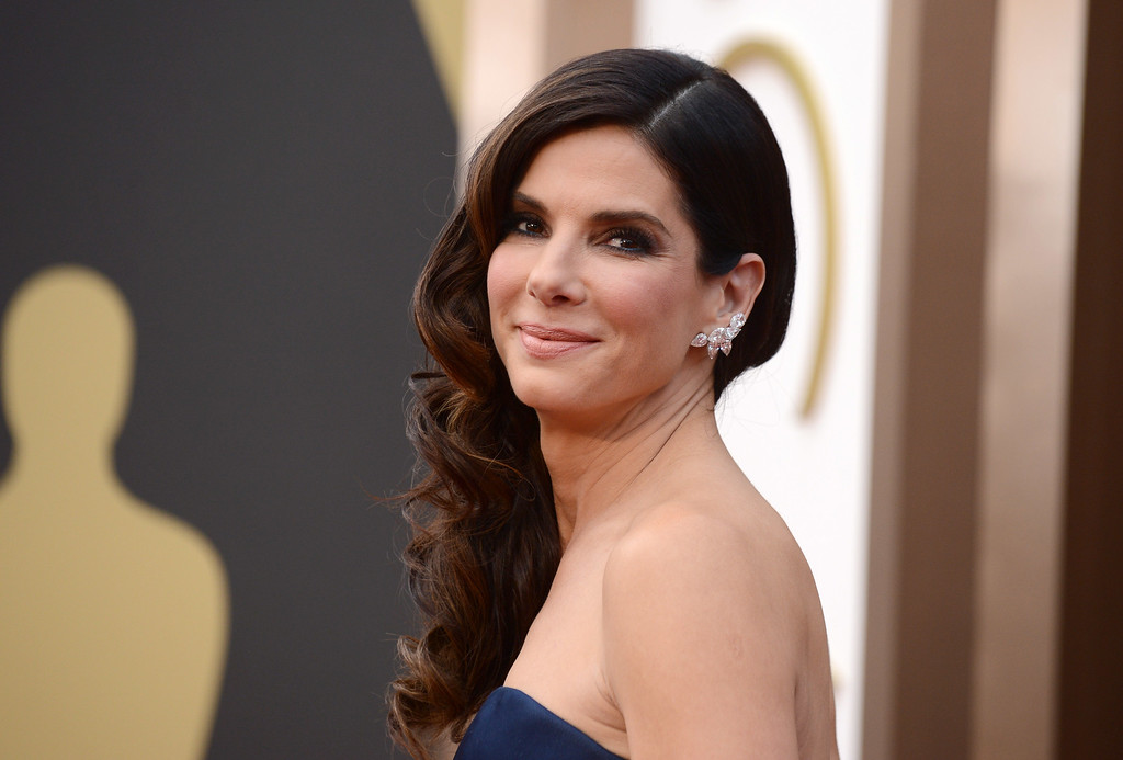 """. Sandra Bullock arrives at the Oscars on Sunday, March 2, 2014, at the Dolby Theatre in Los Angeles.  People magazine has named Bullock as the \""""World\'s Most Beautiful Woman\"""" for 2015. (Photo by Jordan Strauss/Invision/AP)"""