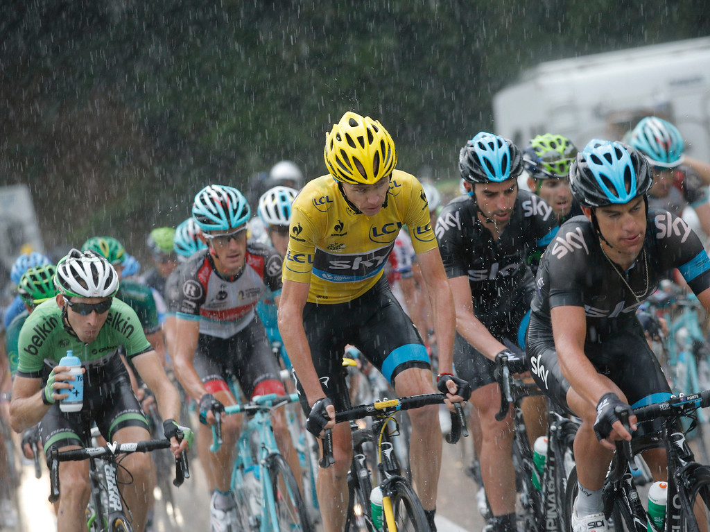 . Christopher Froome of Britain, wearing the overall leader\'s yellow jersey, and Bauke Mollema of The Netherlands, left and drinking, ride in downpour during the nineteenth stage of the Tour de France cycling race over 204.5 kilometers (127.8 miles) with start in in Bourg-d\'Oisans and finish in Le Grand-Bornand, France, Friday July 19 2013. (AP Photo/Christophe Ena)