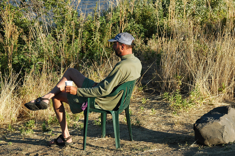 Danny takes a moment before breakfast to enjoy a hot drink and to watch the river roll by.