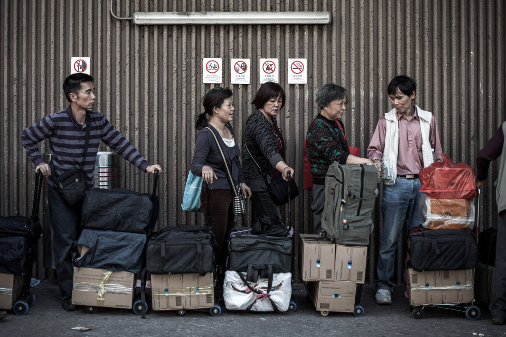 . People queue up to get their packages weighed at the Sheung Shui train station prior to their journey to mainland China on January 30, 2013.  PHILIPPE LOPEZ/AFP/Getty Images