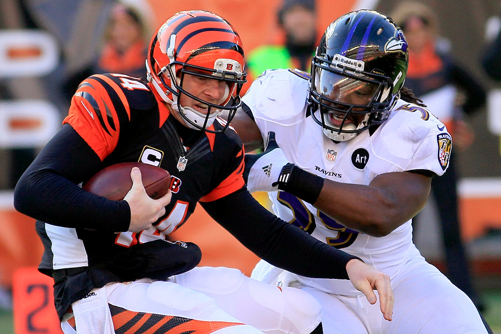 Description of . Cincinnati Bengals quarterback Andy Dalton (14) avoids a sack by Baltimore Ravens inside linebacker Dannell Ellerbe in the first half of an NFL football game, Sunday, Dec. 30, 2012, in Cincinnati. (AP Photo/Tom Uhlman)