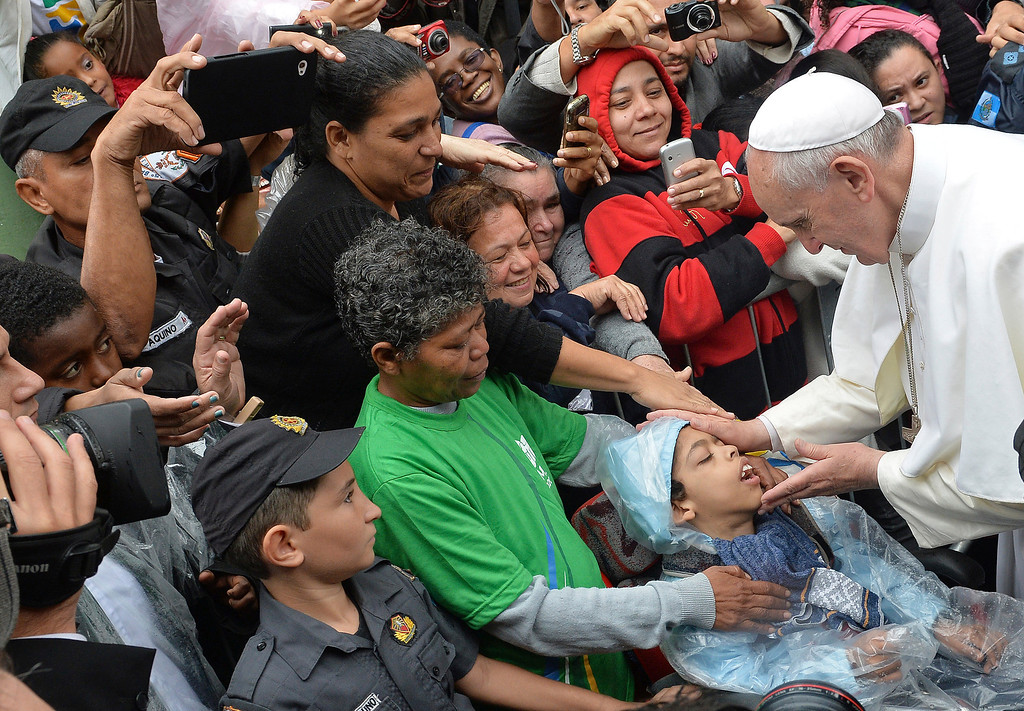. Pope Francis blesses a child during his visit to the Varginha slum in Rio de Janeiro, Brazil, Thursday, July 25, 2013. Francis on Thursday visited one of Rio de Janeiro\'s shantytowns, or favelas, a place that saw such rough violence in the past that it\'s known by locals as the Gaza Strip. (AP Photo/Luca Zennaro, Pool)