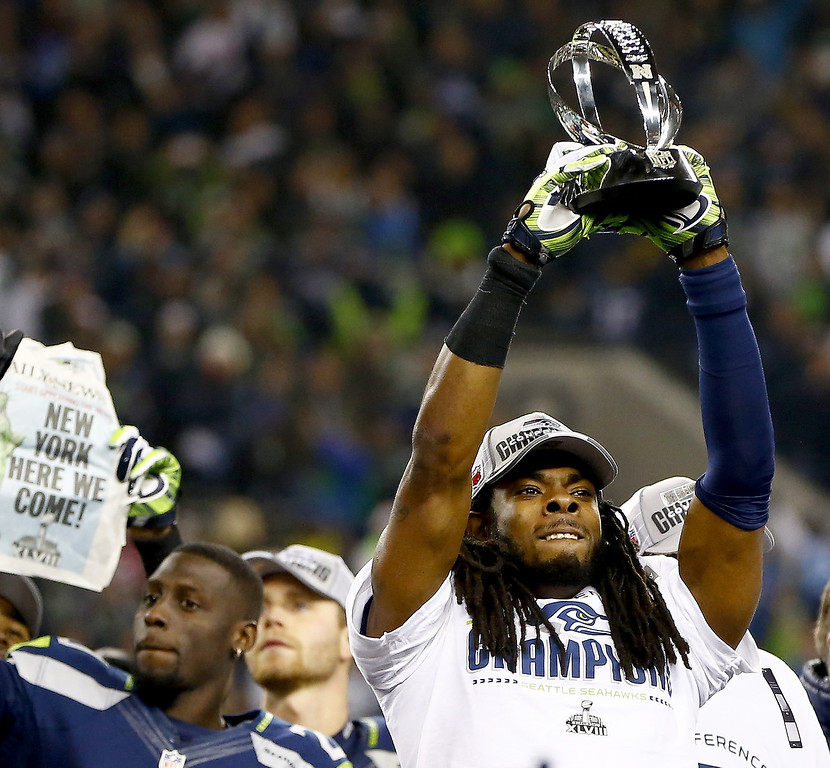 . Cornerback Richard Sherman #25 of the Seattle Seahawks celebrates with the George Halas Trophy after the Seahawks defeat the San Francisco 49ers 23-17 in the 2014 NFC Championship at CenturyLink Field on January 19, 2014 in Seattle, Washington.  (Photo by Jonathan Ferrey/Getty Images)