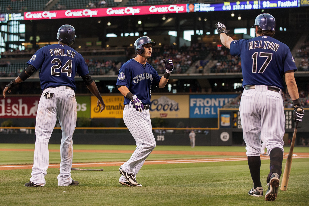 . Corey Dickerson #6, Dexter Fowler #24 and Todd Helton #17 of the Colorado Rockies celebrate a pair of first inning runs against the San Diego Padres during a game at Coors Field on August 12, 2013 in Denver, Colorado. The Rockies led the Padres 2-0 after one inning.  (Photo by Dustin Bradford/Getty Images)