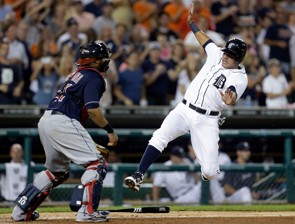 . Detroit Tigers\' Avisail Garcia slides safely into home plate as Cleveland Indians catcher Carlos Santana waits for the throw on a Jhonny Peralta two-run double in the eighth inning of a baseball game in Detroit, Wednesday, Sept. 5, 2012. Detroit won 7-1. (AP Photo/Paul Sancya)