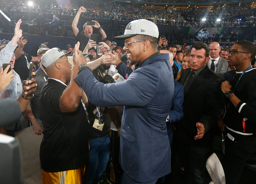 . UTSA\'s Marcus Davenport, center, celebrates with New Orleans Saints fans after being selected by the team during the first round of the NFL football draft, Thursday, April 26, 2018, in Arlington, Texas. (AP Photo/Michael Ainsworth)