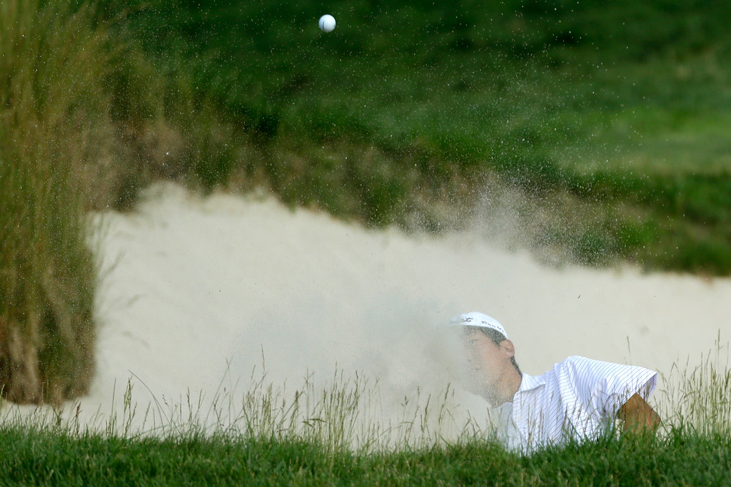 . Michael Kim hits out of a bunker on the 17th hole during the third round of the U.S. Open golf tournament at Merion Golf Club, Saturday, June 15, 2013, in Ardmore, Pa. (AP Photo/Julio Cortez)