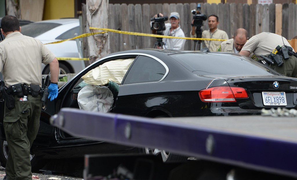 ". Investigators inspect a suspected gunman\'s car on May 24, 2014, after a drive-by shooting in Isla Vista, California, a beach community next to the University of California Santa Barbara. Seven people, including the gunman, were killed and seven others wounded in the May 23 mass shooting, Santa Barbara County Sheriff Bill Brown said Saturday. Brown said at a pre-dawn press conference that the shooting in the town of Isla Vista ""appears to be a mass murder situation.\"" Driving a black BMW, the suspect opened fire on pedestrians from his vehicle at several locations in the town.            (ROBYN BECK/AFP/Getty Images)"